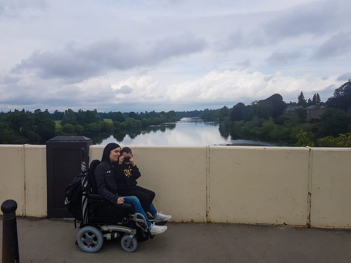 Emma driving her wheelchair across the Perth Bridge while her young nephew sits on a her lap. He is holding a camera up at his face taking a photo of the person taking his photo.