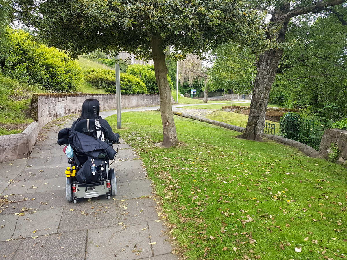 Emma, driving her wheelchair ion a path down towards a park. There are trees on each side.