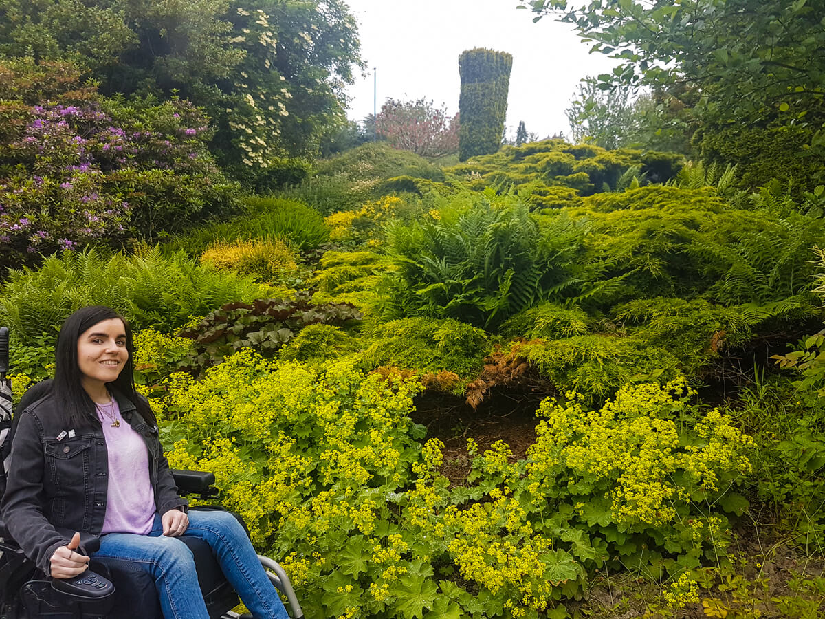 Emma, a powered wheelchair user is sitting next to green plants and shrubs.