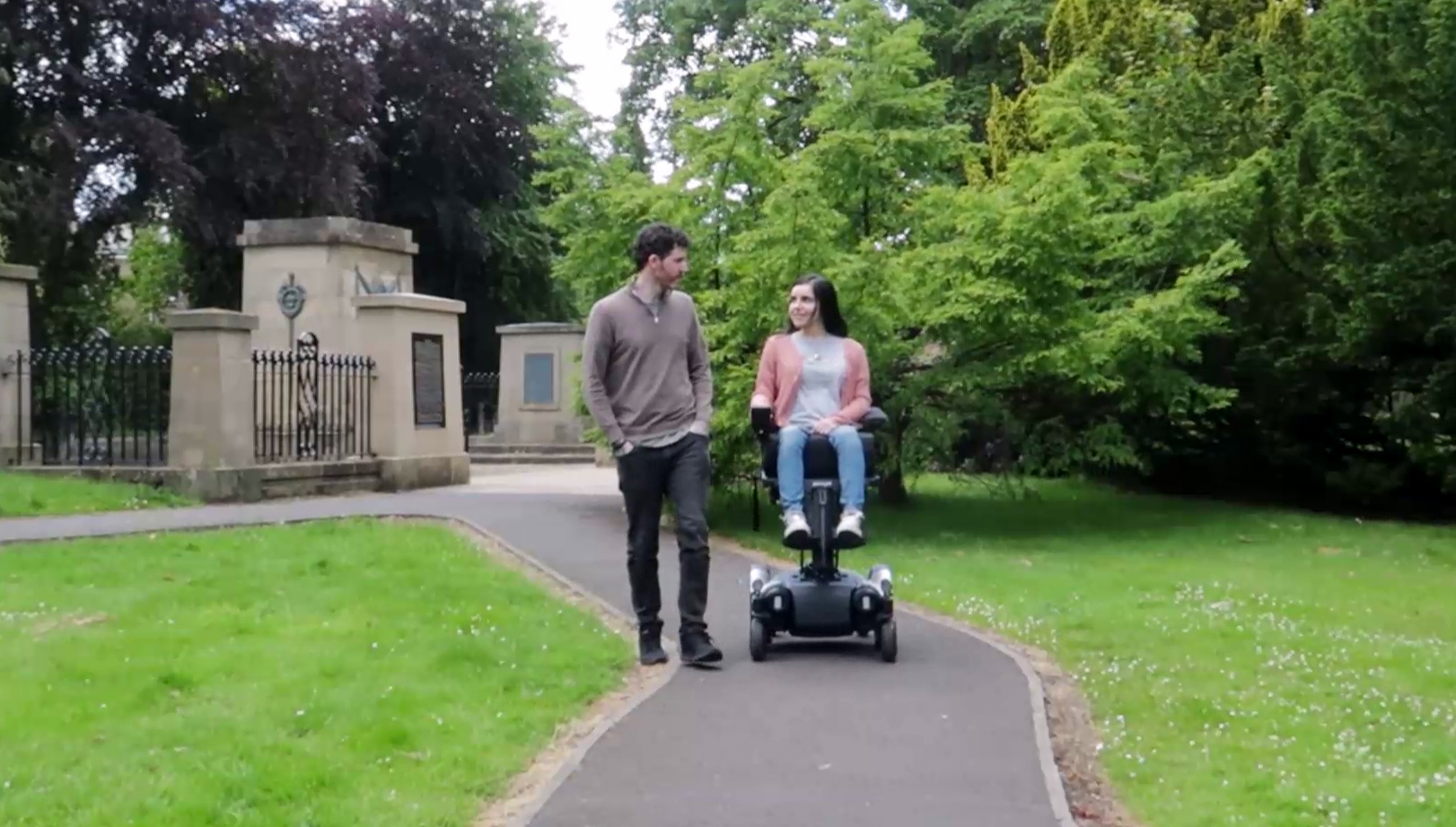Emma is driving along a path in a park with her wheelchair elevated. Allan is walking along next to her. They are both at the same height.
