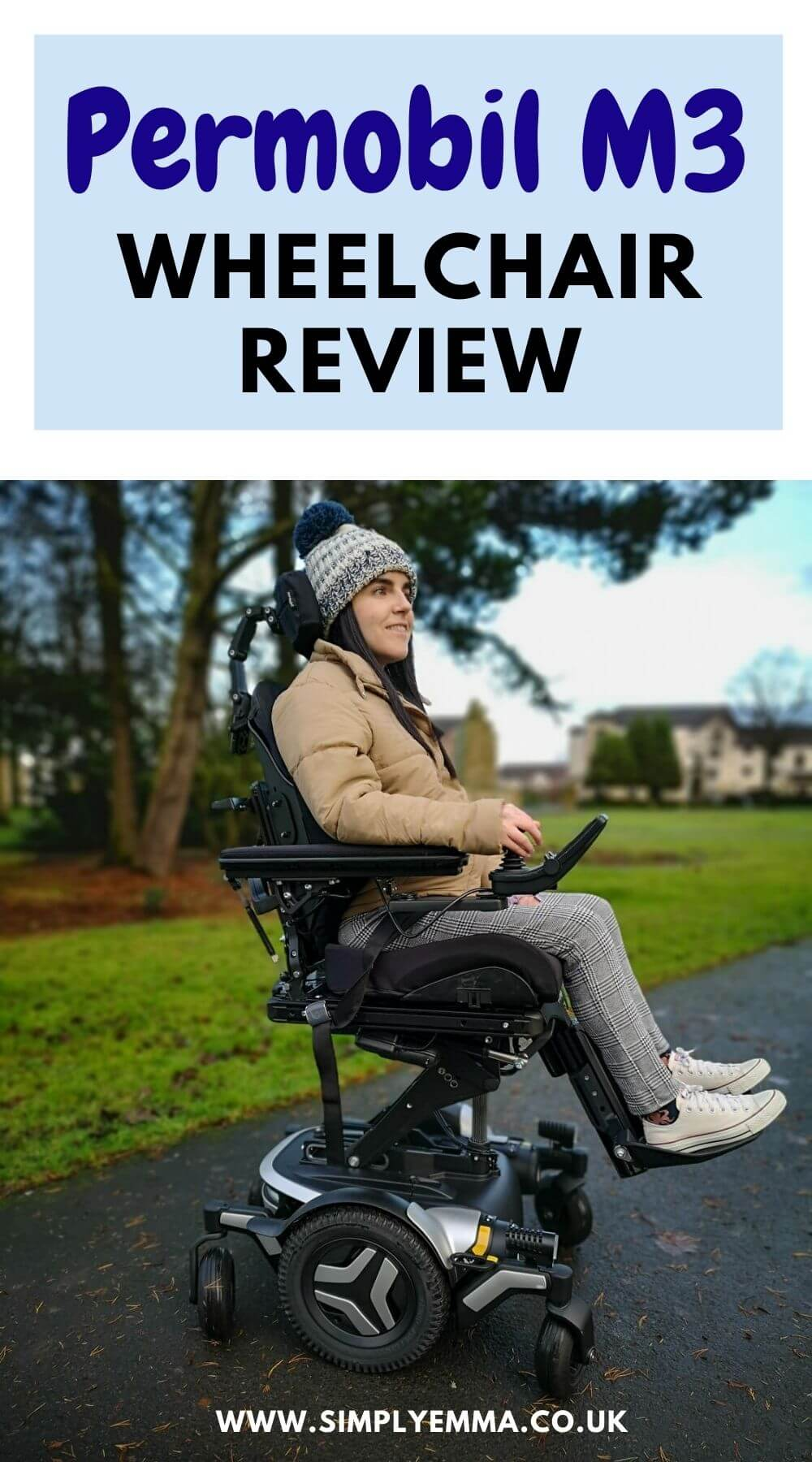 """Emma, a wheelchair user sitting in a black and silver Permobil M3 wheelchair in a park. She is wearing a woolly hat, puffy jacket, black and white check trousers and white converse shoes. The wheelchair seat is elevated. Emma is smiling. Text reads """"Permobilo M3 Wheelchair Review. www.simplyemma.co.uk"""""""