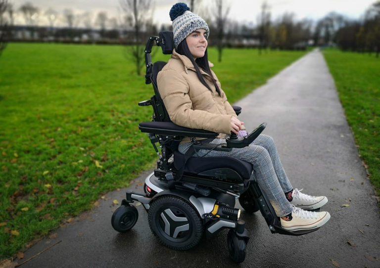 Emma, a wheelchair user sitting in a black and silver Permobil M3 wheelchair in a park. She is wearing a woolly hat, puffy jacket, black and white check trousers and white converse shoes. Emma is smiling.