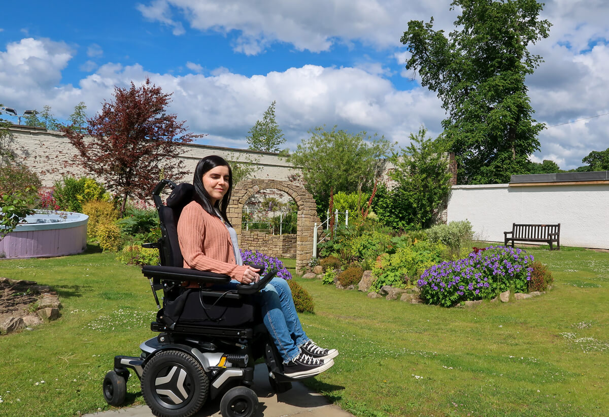 Emma driving her Permobil powerchair in the park. She is wearing a grey t-shirt, peach cardigan, blue jeans and black converse shoes. She is surrounded by lush shrubbery.