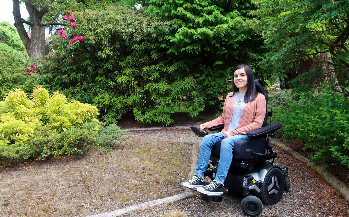 Emma driving her Permobil powerchair in the park. She is wearing a grey t-shirt, peach cardigan, blue jeans and black converse shoes. She is surrounded by lush shrubbery. The ground is covered in small gravel stones.