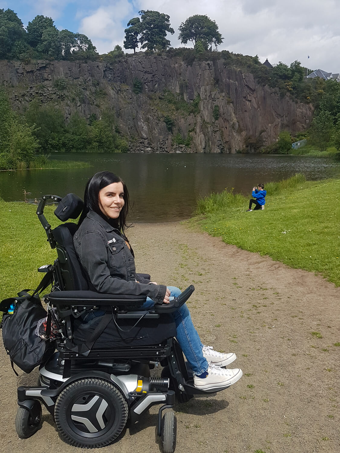 Emma, a wheelchair user sitting in a black and silver Permobil M3 wheelchair with a reservoir behind her.