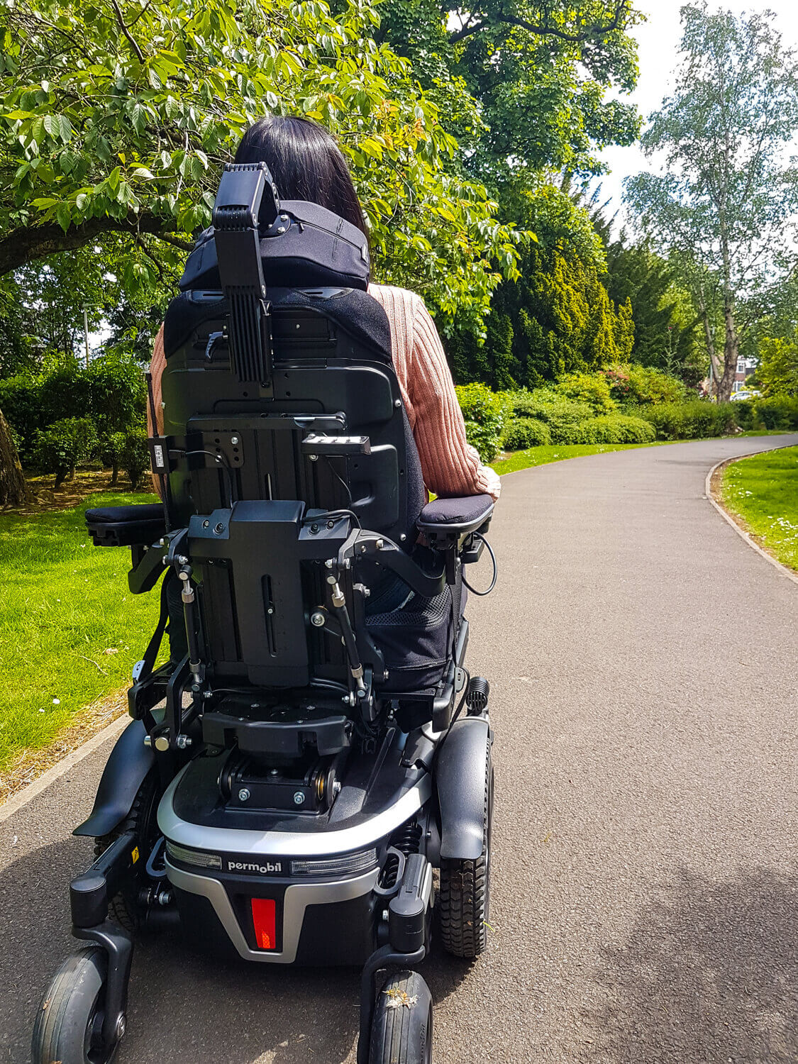 Emma, a wheelchair user sitting in a black and silver Permobil M3 wheelchair in a park. Emma has her back towards the camera showing the back of the wheelchair. She is driving along a wheelchair accessible path in a park. Trees are in the background.