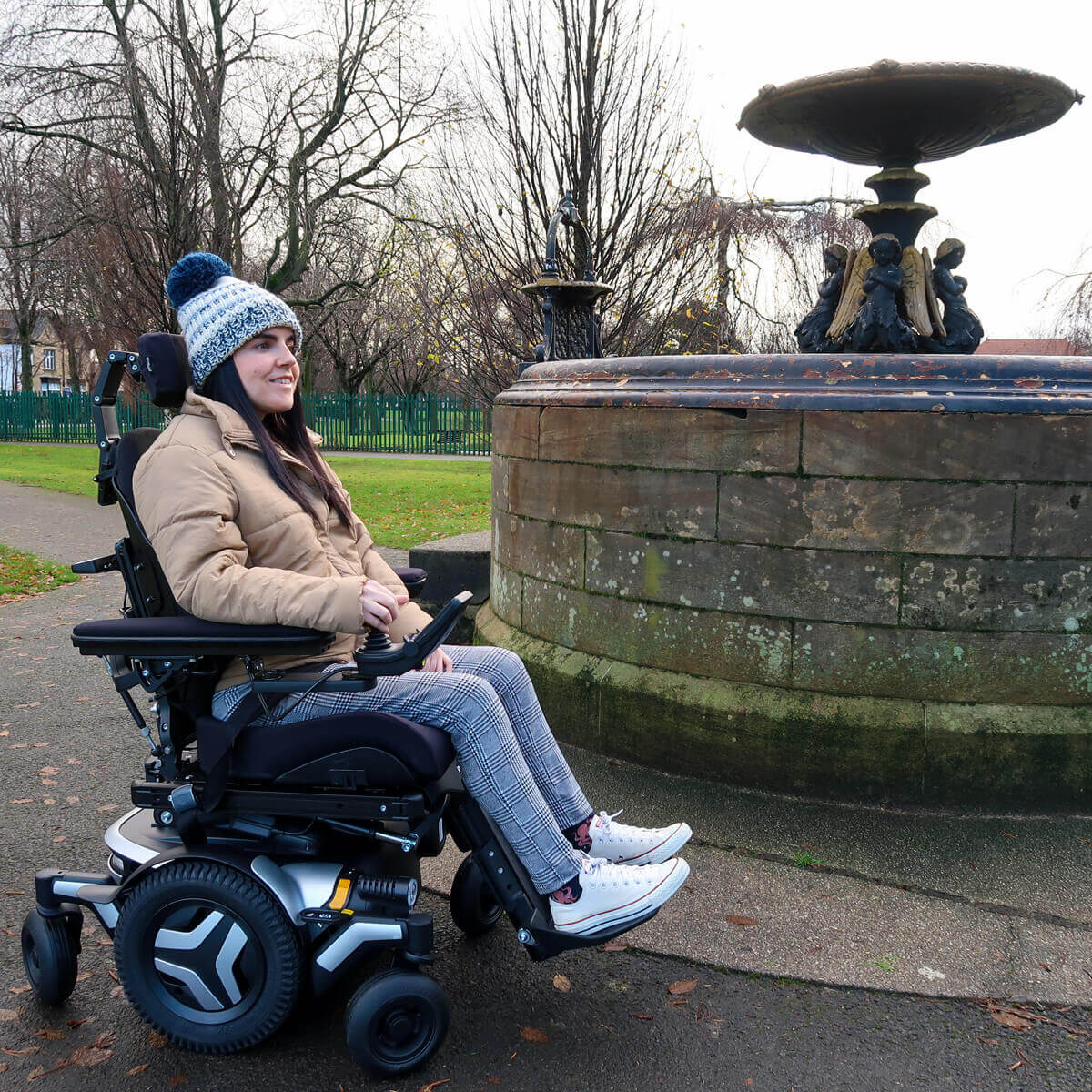 Emma, a wheelchair user sitting in a black and silver Permobil M3 wheelchair in a park. She is sitting next to an old water fountain in a park. She is wearing a woolly hat, puffy jacket, black and white check trousers and white converse shoes. Emma is smiling.