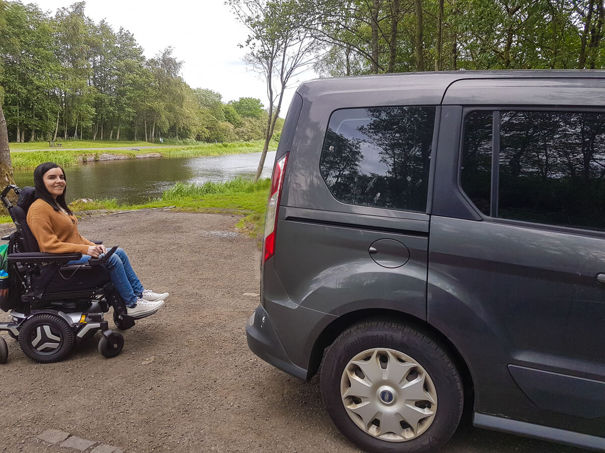Emma is smiling at the camera while outdoors next to a river. She facing towards her wheelchair accessible vehicle.