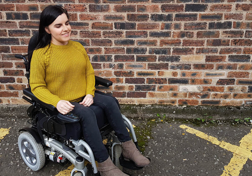 Emma sitting in her powered wheelchair wearing a mustard coloured jumper, black skinny jeans and brown boots. She is sitting in front of a brick wall outside.