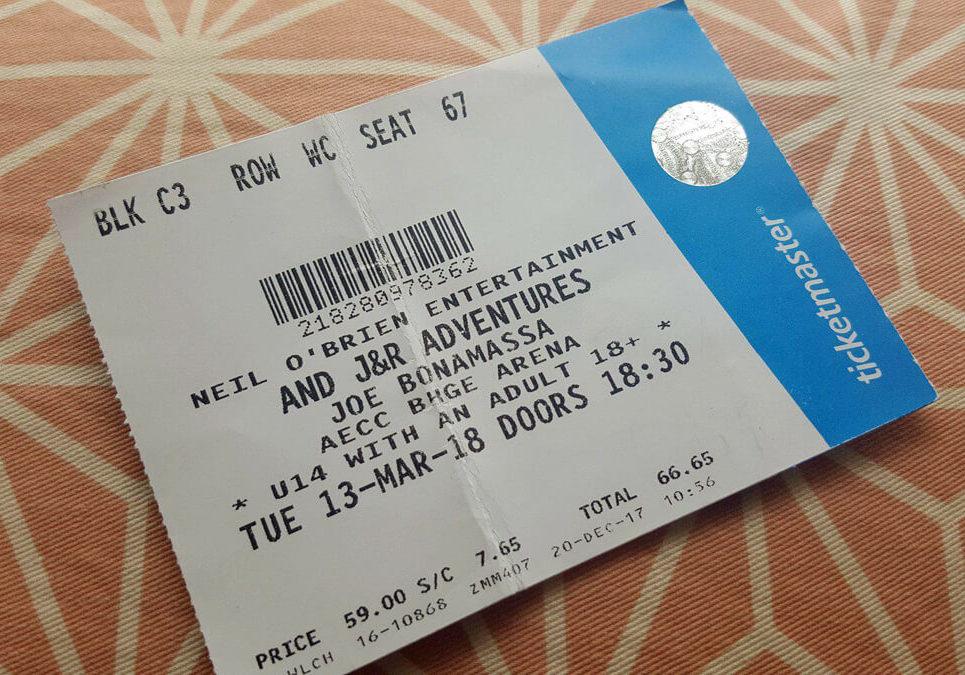 A ticket for Joe Bonamassa gig at AECC Aberdeen laying flat on a peach coloured geometric cushion