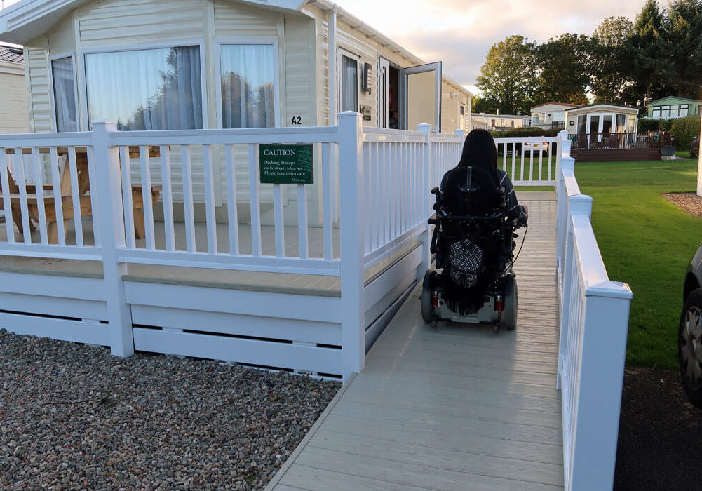 Emma driving her powered wheelchair up the ramp of the wheelchair accessible caravan.
