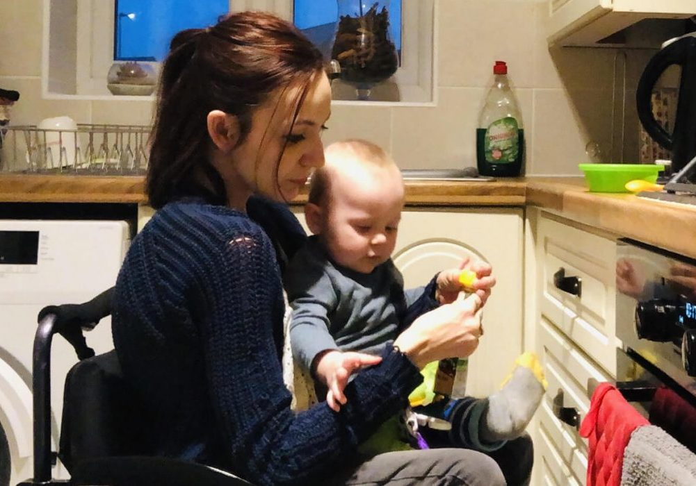 Molly is sitting in her manual wheelchair in her kitchen. Her young son is sitting on her lap.