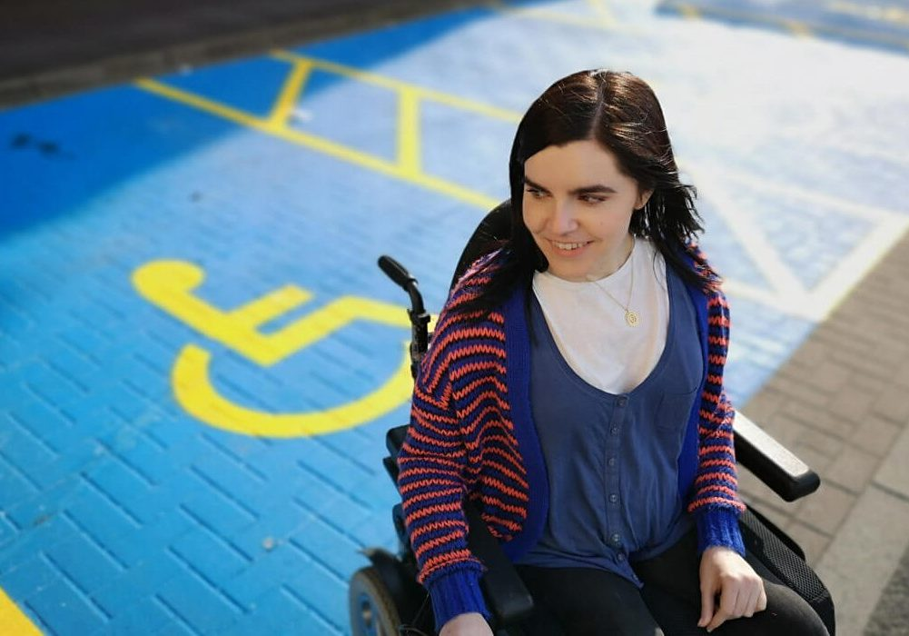 Emma is in her powered wheelchair. Her face is slightly facing to the side, looking down and smiling. Her dark hair is blowing in the wind. She is sitting in a disabled parking bay in her wheelchair.