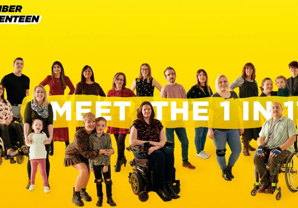 "A yellow background with seventeen people with a range of rare conditions posing. A banner is floating across the photo with the words ""Meet the 1 in 17"".I Am Number 17"