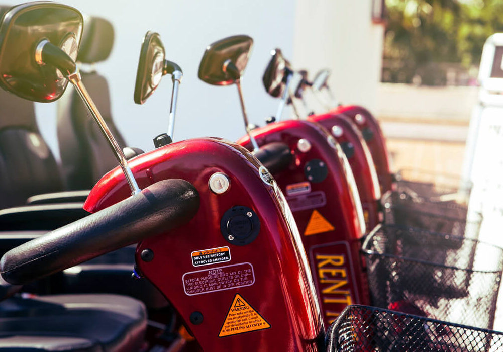A close up of red mobility scooters lined up in a row.