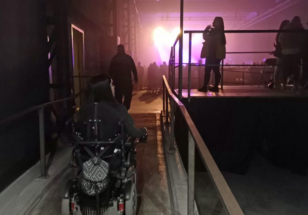 Emma driving up a concrete ramp in her wheelchair in SWG3.