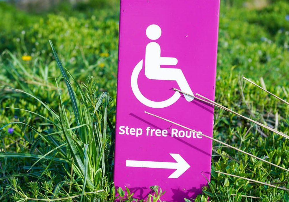 "A pink sign stuck in the grass with a white wheelchair symbol. Text reads ""step-free route"" with an arrow pointing to the right."