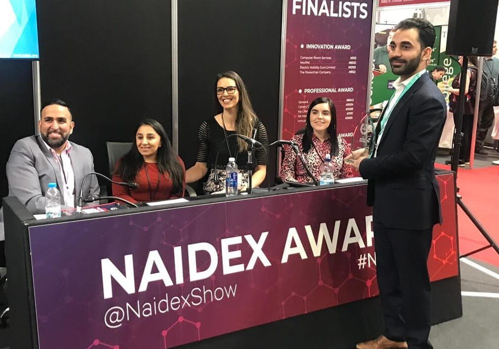 Emma sitting behind the judging panel at Changing Lives Award at Naidex.