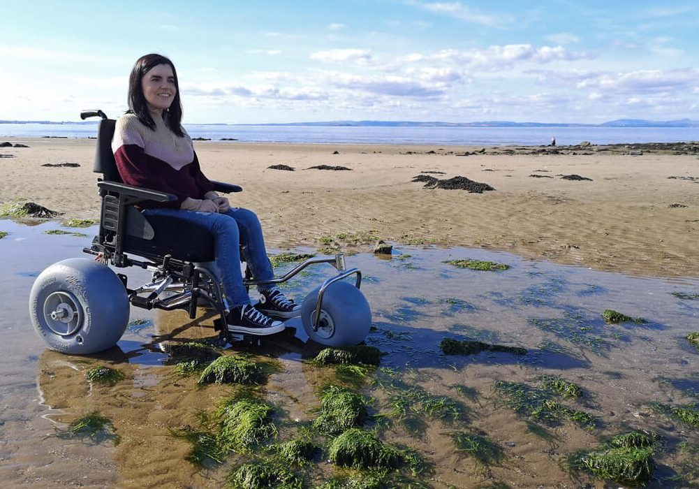 Emma sitting in the WheelEEZ® Beach Wheelchair Conversion Kit.