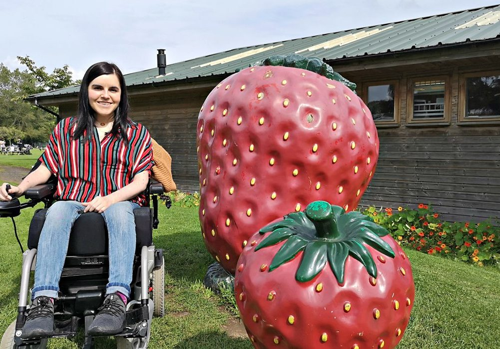 Emma sitting next to giant strawberry statues.