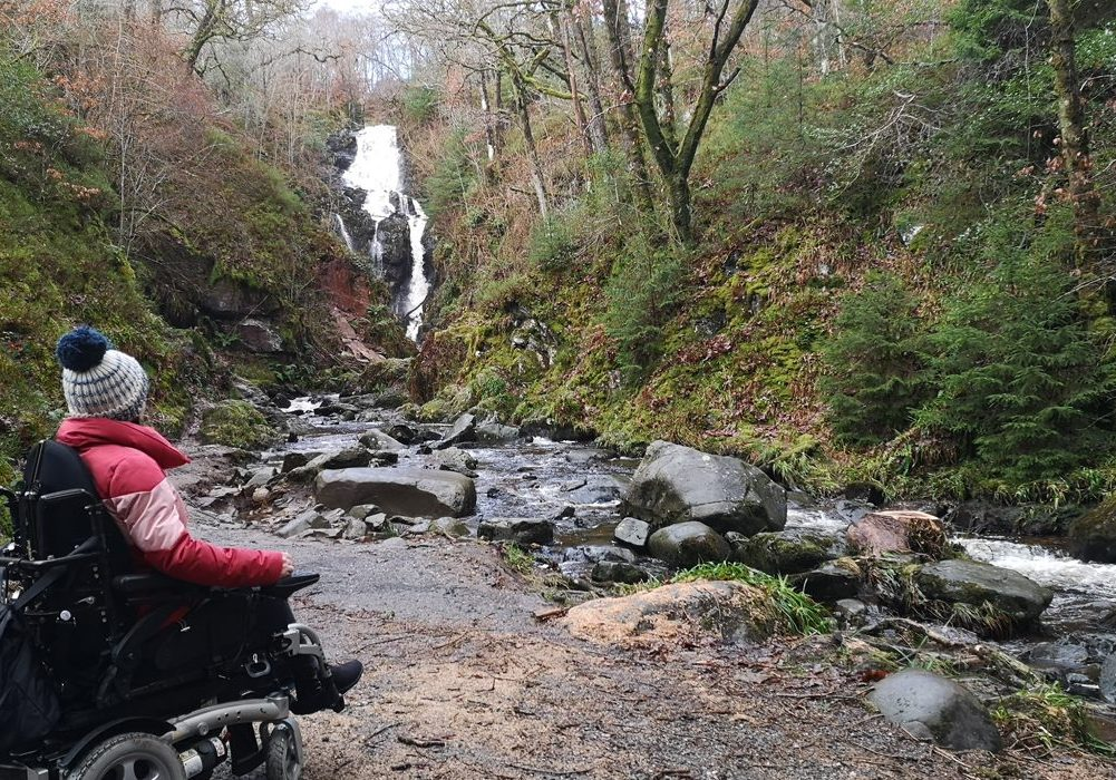Emma in her wheelchair looking across a river to the waterfall.
