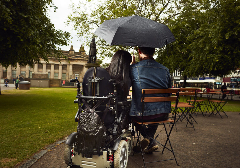 Emma sitting in her wheelchair with Allan. They are both sitting in Princes Street Gardens in Edinburgh. Emma has her head gently resting on Allan's shoulder.