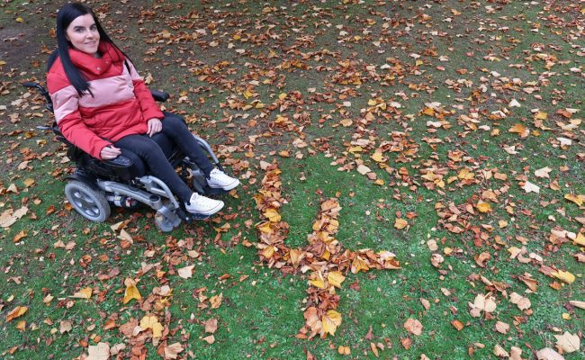 Emma is wearing a pink/red puffy jacket, black jeans and white converse shoes while sitting in her powered wheelchair. She is in her local park. She is sitting beside a giant number four shaped out of leaves.