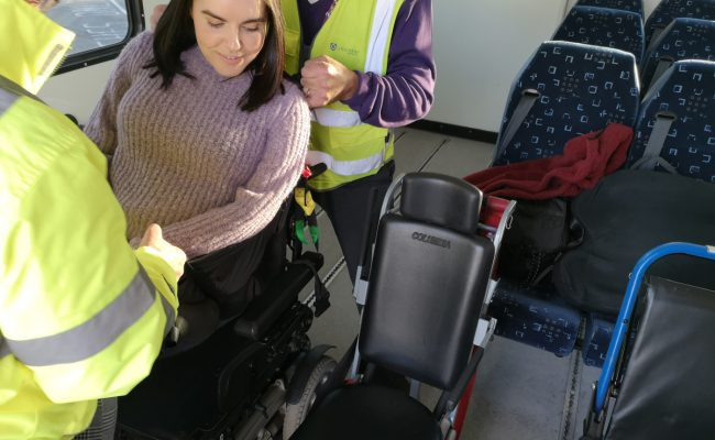 Emma being lifted out of her wheelchair by two special assistance workers.