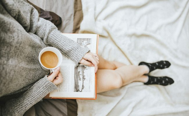 A woman sitting reading a book while holding a cup of tea.