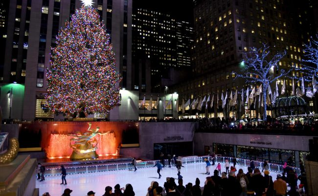 A view overlooking the ice rink and Rockefeller Centre Christmas Tree at night.