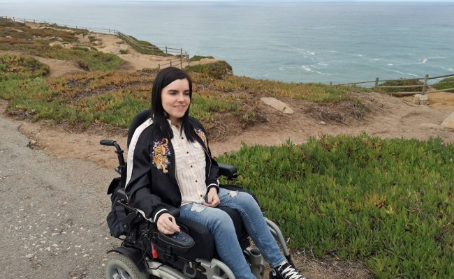 Emma in her wheelchair sitting with the ocean behind her in Portugal.