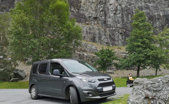 A Ford Tourneo Connect wheelchair accessible vehicle parked beside a rock wall. Emma is sitting beside the vehicle too.