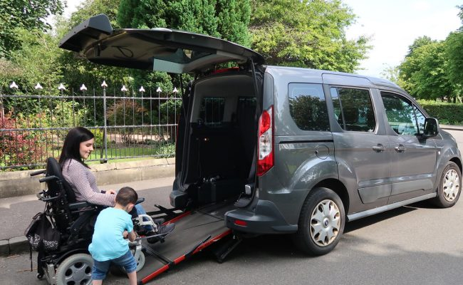 Emma is sitting in her wheelchair at the bottom of her wheelchair accessible vehicle while her nephew is securing belts onto her wheelchair.